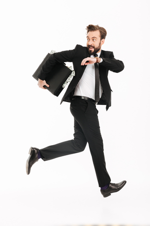 Photo pour Image of excited young businessman with suitcase running isolated over white background. Looking aside. - image libre de droit