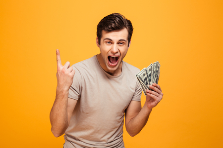 Photo pour Portrait of an excited young man holding money cash and celebrating isolated over yellow background - image libre de droit