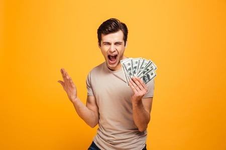 Foto de Portrait of a happy young man holding money cash and celebrating isolated over yellow background - Imagen libre de derechos