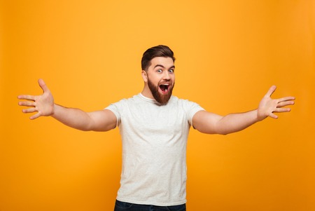 Foto de Portrait of a cheerful bearded man with outsretched hands isolated over yellow background - Imagen libre de derechos
