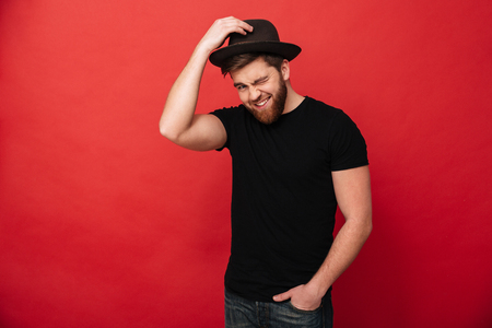 Photo for Portrait of charming caucasian man wearing black outfit touching his hat and winking while standing with hand in pocket isolated over red background - Royalty Free Image