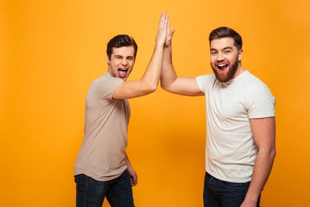 Foto de Portrait of a two delighted young men celebrating with high five gesture isolated over yellow background - Imagen libre de derechos