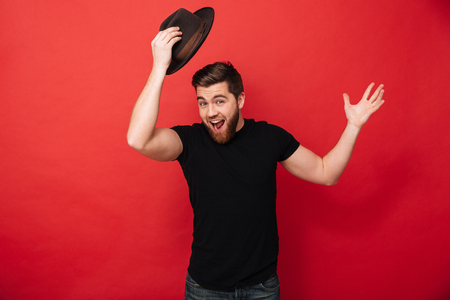 Photo pour Portrait of amusing bearded man wearing black outfit posing on camera and greeting with taking off hat isolated over red background - image libre de droit