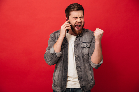 Photo for Photo of handsome excited man expressing surprise on face and clenching fist like winner while having mobile conversation isolated over red background - Royalty Free Image