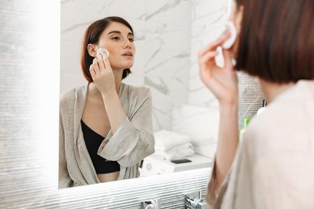 Photo pour Beauty portrait of brunette woman with cosmetics on face removing makeup with cotton pad at home bathroom - image libre de droit