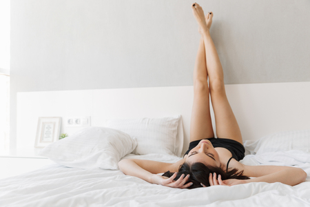 Foto für Portrait of a beautiful young woman lying on bed with legs up on bed at the bedroom - Lizenzfreies Bild