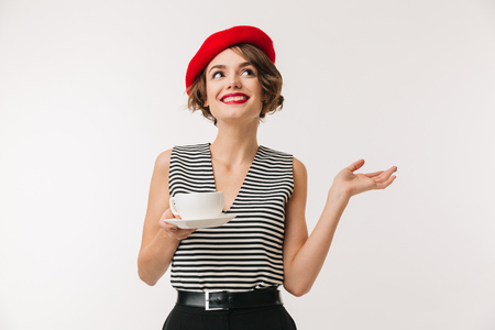 Photo pour Portrait of elegant woman in striped shirt and red beret and holding cup of hot tea with hand aside isolated over white background - image libre de droit