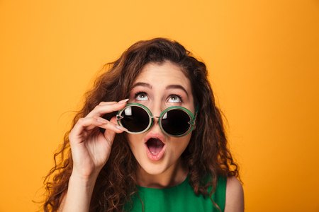Photo pour Image of shocked young lady standing isolated over yellow background. Looking aside wearing sunglasses. - image libre de droit