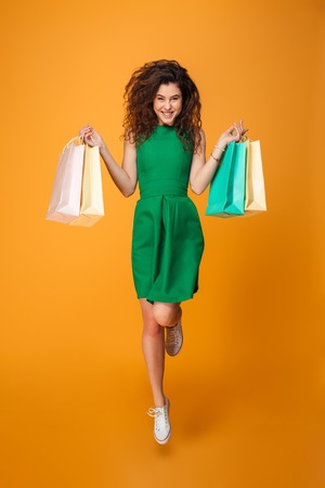 Photo pour Image of happy young woman standing isolated over yellow background. Looking camera holding shopping bags. - image libre de droit