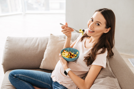 Foto de Pretty pregnant young woman having healthy breakfast while sitting on a couch - Imagen libre de derechos