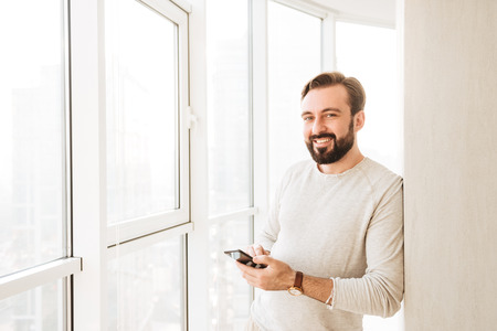 Photo for Photo of candid brunette guy 30s in white shirt, spending time near big window and holding mobile phone - Royalty Free Image