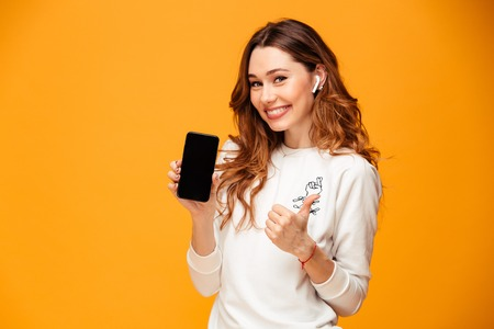 Photo pour Image of cheerful young woman standing isolated over yellow background listening music showing display of mobile phone make thumbs up. - image libre de droit