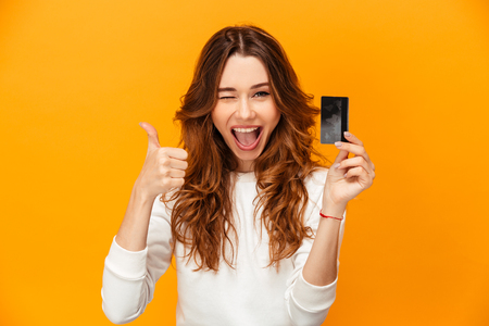 Foto de Cheerful brunette woman in sweater showing thumb up and holding credit card while winks and looking at the camera over yellow background - Imagen libre de derechos