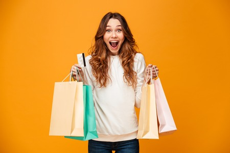 Foto de Image of excited screaming young woman standing isolated over yellow background looking camera holding shopping bags and credit card. - Imagen libre de derechos