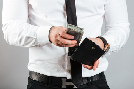 Foto de Close up of a rich man putting cash in his wallet isolated over gray background - Imagen libre de derechos