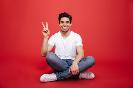 Photo pour Portrait of a friendly young man in white t-shirt sitting on a floor and showing peace gesture isolated over red background - image libre de droit