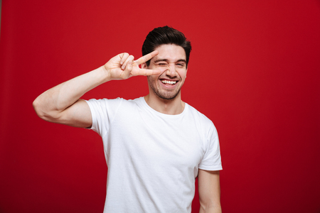 Foto de Portrait of a happy young man in white t-shirt showing peace gesture isolated over red background - Imagen libre de derechos