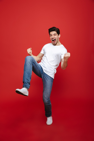 Foto de Full length portrait of a happy young man in white t-shirt celebrating success isolated over red background - Imagen libre de derechos