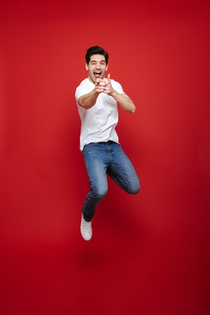 Foto de Full length portrait of a happy young man in white t-shirt pointing fingers at camera while celebrating success isolated over red background - Imagen libre de derechos