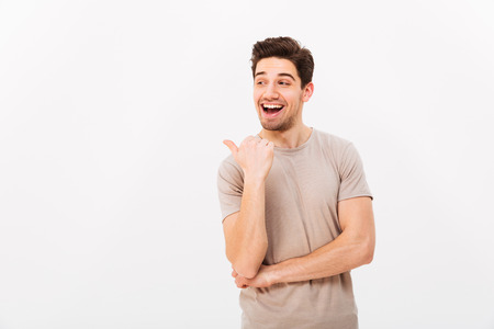 Foto per Handsome man 30s with brown hair wearing beige t-shirt gesturing finger aside on copyspace isolated over white background - Immagine Royalty Free