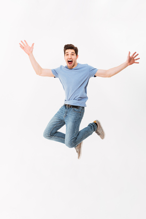 Photo pour Full-length photo of funny man 30s in casual t-shirt and jeans jumping with arms throwing up isolated over white background - image libre de droit