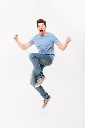 Foto de Full-length photo of excited man 30s in casual t-shirt and jeans levitating while expressing triumph with clenching fists isolated over white background - Imagen libre de derechos