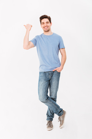 Photo pour Full-length image of handsome man rejoicing and pointing finger aside on copyspace isolated over white background - image libre de droit