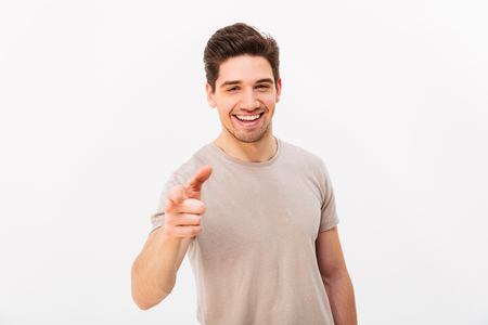 Photo pour Confident cheerful man with brown hair gesturing index finger on camera meaning hey you isolated over white background - image libre de droit