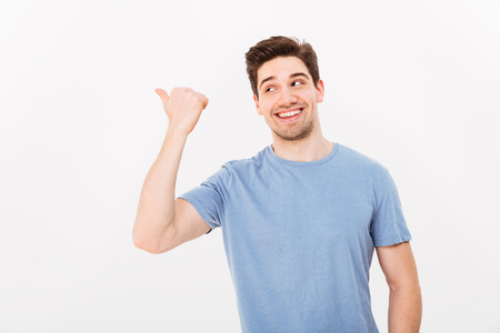 Foto de Closeup image of man with shining smile in casual clothing pointing finger aside on copyspace text or product isolated over white background - Imagen libre de derechos