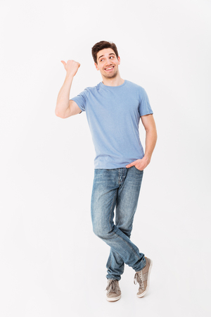 Foto de Full-length image of man in good mood presenting text or product with pointing finger aside on copyspace isolated over white background - Imagen libre de derechos