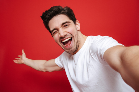Foto de Portrait of an excited young man in white t-shirt showing peace gesture while taking a selfie isolated over red background - Imagen libre de derechos