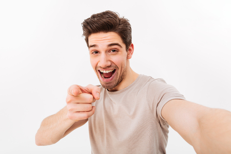 Photo for Studio photo of positive man in casual t-shirt and bristle on face smiling and pointing finger on camera while taking selfie isolated over white background - Royalty Free Image