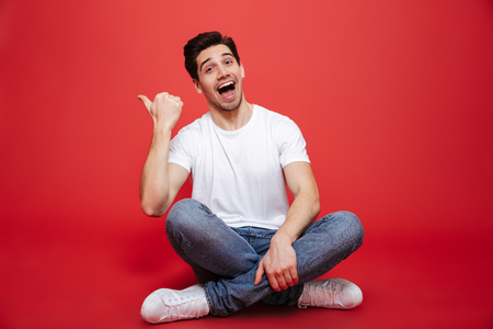 Photo pour Portrait of a joyful young man in white t-shirt sitting on a floor and pointing finger away isolated over red background - image libre de droit