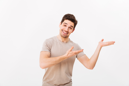Foto de Cheerful guy in casual t-shirt advertising and presenting copyspace text or product on palm with broad smile isolated over white background - Imagen libre de derechos