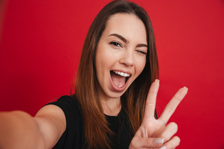 Foto de Cute woman 20s in black t-shirt having fun and taking selfie with gesturing peace sign isolated over red background - Imagen libre de derechos