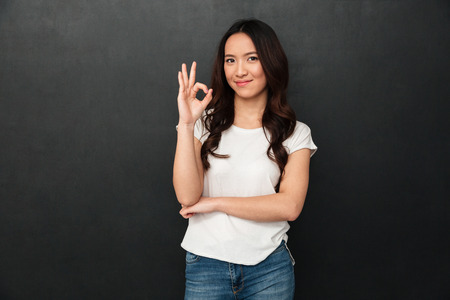 Photo for Portrait of asian cute woman in casual t-shirt and jeans smiling and showing ok or alright sign, isolated over dark gray background - Royalty Free Image