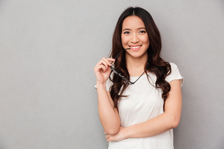 Foto de Happy asian woman in t-shirt bites eyeglasses and looking at the camera over grey background - Imagen libre de derechos