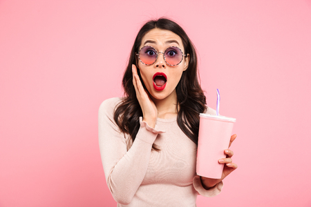 Photo for Photo of thrilled adult girl with long dark hair in round glasses holding cold beverage in paper cup isolated over pink background - Royalty Free Image
