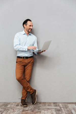 Photo for Full length portrait of a smiling mature man dressed in shirt using laptop computer while standing over gray background - Royalty Free Image