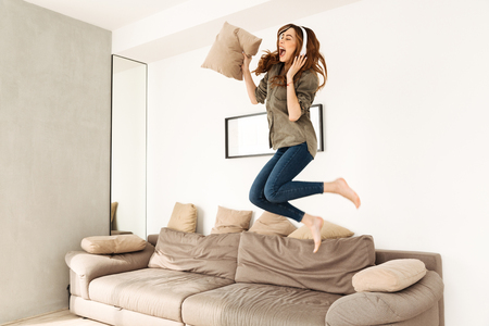 Foto de Joyful woman 20s in casual clothing playing around in cozy apartment and jumping on sofa while listening to music via wireless headphones - Imagen libre de derechos
