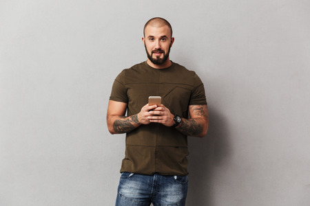 Photo for Unshaved man 30s in casual clothes looking on camera while using smartphone holding in hand isolated over gray background - Royalty Free Image