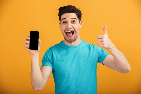 Foto de Portrait of a happy young man in t-shirt holding blank screen mobile phone and showing thumbs up isolated over yellow background - Imagen libre de derechos