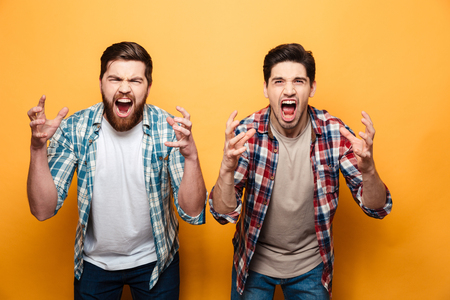 Foto de Portrait of a two angry young men shouting loud isolated over yellow background - Imagen libre de derechos