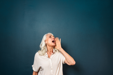 Photo pour Photo of serious mature old woman isolated over dark blue background. Looking aside screaming talk to someone. - image libre de droit