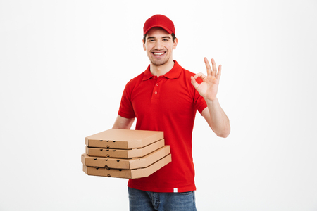 Photo pour Deliveryman 25y in red t-shirt and cap holding stack of pizza boxes and showing ok sign isolated over white background - image libre de droit