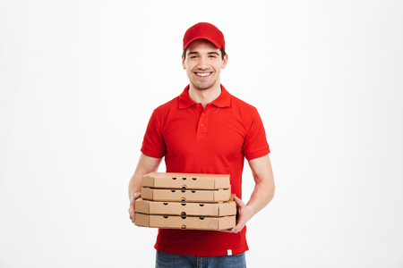Photo pour Image of smiling deliveryman in red t-shirt and cap holding stack of pizza boxes isolated over white background - image libre de droit
