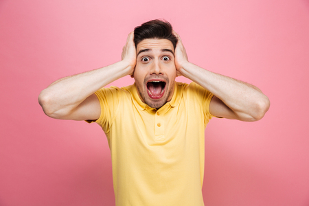 Photo for Portrait of a surprised young man looking at camera with open mouth isolated over pink background - Royalty Free Image