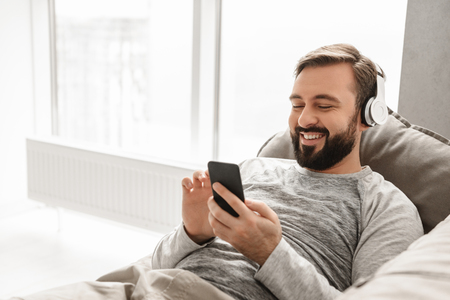 Photo for Positive man 30s in basic clothing lying on sofa in house and listening to music using black cell phone wearing wireless headphones - Royalty Free Image
