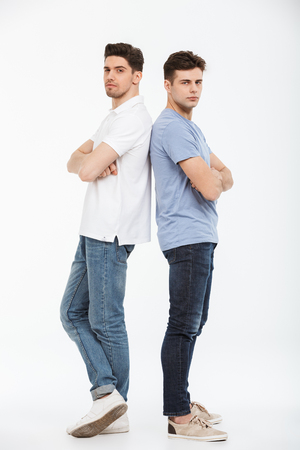 Foto de Full length portrait of two upset young men standing back to back with arms folded isolated over white background - Imagen libre de derechos