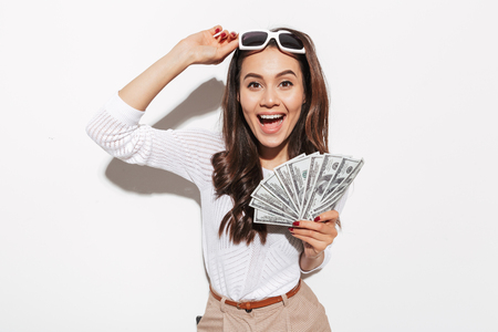Foto de Portrait of a cheerful young asian businesswoman in sunglasses showing money banknotes and celebrating isolated over white background - Imagen libre de derechos